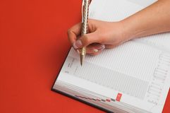 Female is writing notes. Red background Stock Images