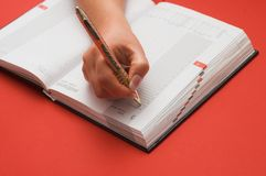 Female is writing notes. Red background Stock Photos