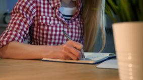 Female writing with pen in notepad. Crop view of woman with long blond hair in bright casual shirt sitting at wooden stock video footage