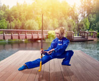 Female wushu fighter with blade against lake Stock Photography