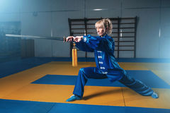 Female wushu fighter with sword in action. Martial arts. Woman in blue cloth poses with blade Royalty Free Stock Images