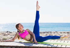Female 30-40 years old is practicing yoga. On the beach near sea Stock Images