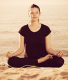 Female 20-30 years old is sitting and doing meditation in black. T-shirt on the beach Royalty Free Stock Images