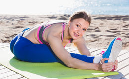 Female 30-40 years old is stretching. On the beach near sea royalty free stock photography