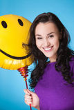 Female with yellow baloon. Attractive female with yellow baloon isolated on blue stock photography