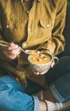 Woman sitting and eating pumpkin soup from mug stock photos