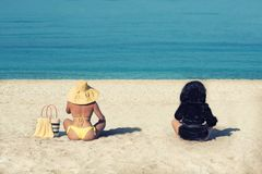 Female in a yellow swimsuit and hat and a girl in a fur coat on the beach. Conceptual picture of winter and summer. Winter is leav. Ing. Summer is gone. Two Stock Image