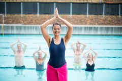 Female yoga instructor assisting senior swimmers at poolside Royalty Free Stock Photos