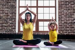 Female yoga instructor training little girl doing stretching exercise sitting in lotus position indoors Stock Images