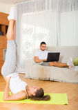 Female in yoga position and lazy guy on sofa Stock Photos