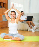 Female in yoga position and lazy guy on sofa. At home Royalty Free Stock Photo