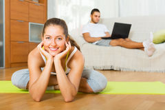 Female in yoga position and lazy guy on sofa. Smiling female in yoga position and lazy guy with laptop on sofa Stock Images