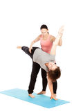 Female yoga teacher provides assistance Royalty Free Stock Photos