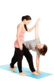 Female yoga teacher provides assistance Stock Image