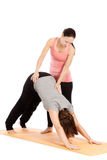Female yoga teacher provides assistance Stock Photography