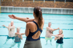 Female yoga trainer instructing senior swimmers. Rear view female yoga trainer instructing senior swimmers at poolside Royalty Free Stock Photos