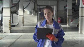 Young woman assistance writing important information about car fro test and control in modern car service. Female young assistance writing important datas about stock footage