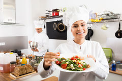Female young cook holding plate Royalty Free Stock Images