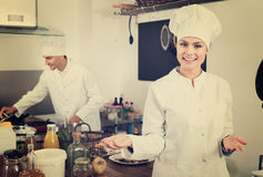 Female young cook wearing uniform working Stock Photos