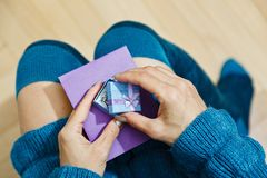 Female young person opening gift box. Young woman dressed in warm blue dress and high socks unpacking the present - opening gift box with jewelry and holding Stock Image