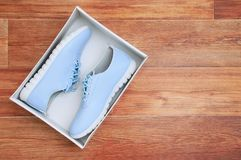 Female youth blue sneakers in a cardboard box on the floor. On brown wooden background royalty free stock images