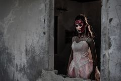 Female zombie corpse standing in front of grunge wall in abandoned house. Horror and Ghost concept. Halloween day festival and stock images