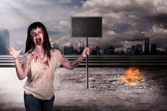 Female zombie holding wooden board over city on fire Royalty Free Stock Photos