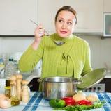 Femalel que cocina la sopa Fotos de archivo