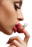 Femalel stellen mit einer Erdbeere gegenüber stockbilder