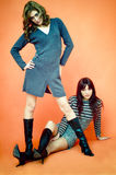 Females With Attitude. Two young women with confident attitudes. One is standing; the other is sitting with her legs stretched out between the standing woman's stock images