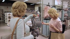 Females choosing brassiere in underwear department stock video footage
