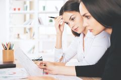 Females doing paperwork. Portrait of two beautiful caucasian females doing paperwork at workplace Stock Photography