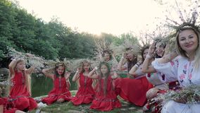 Females in embroidery and floral wreaths waving hands, national traditions, young women in Ukrainian costumes. Kherson, Ukraine - 8 July 2017: Festival of summer stock footage