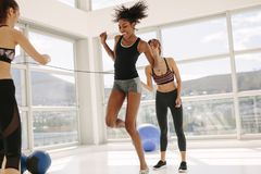 Females enjoying jumping rope workout at gym. Woman jumping rope with friends rotating the rope in fitness studio. Females enjoying jumping rope workout at gym Royalty Free Stock Images