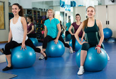 Females with fitness ball at gym. Cheerful females in fitness club having aerobic exercises with Swiss ball. Selective focus Royalty Free Stock Photos