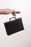Females hand with handcuff and a suitcase Stock Photo