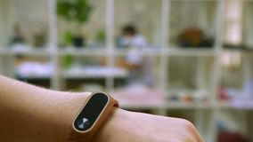 Females hand, showing sittings on her fitness tracker, office concept in office, healthy modern illustration. Females hand, showing sittings on her fitness stock footage