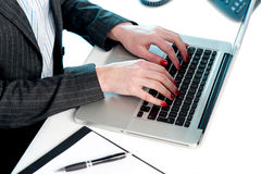 Females hands typing on laptop. Keypad. Cropped image. Busy office desk royalty free stock photography