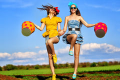 Females jumping with  buckets Stock Photo