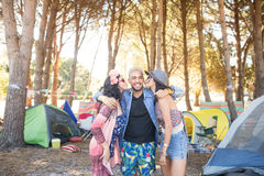 Females kissing male friends standing at campsite Royalty Free Stock Photos