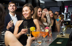 Females and males celebrating corporate. Happy females and males celebrating corporate in the bar at night Royalty Free Stock Image