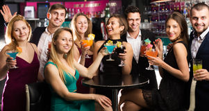 Females and males celebrating corporate. Portrait of happy females and males celebrating corporate in the bar at night Stock Images