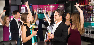 Females and males celebrating corporate. Positive females and males celebrating corporate in the bar at night Royalty Free Stock Images