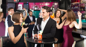 Females and males celebrating corporate. Positive young females and males celebrating corporate in the bar at night Royalty Free Stock Photos