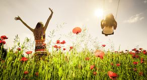 Females in a poppy field on Swing royalty free stock photo