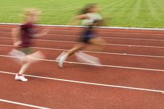 Females Racing on the Track. Blurred motion of two females racing on the track Stock Photo