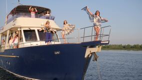 Females ride at yacht and dancing and wind develops clothes on board on river at vacation. Kherson, Ukraine - 28 July 2017: rich females ride at yacht and stock video footage