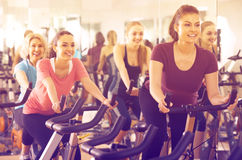 Females riding stationary bicycles. American females riding stationary bicycles in modern gym for women Royalty Free Stock Photography