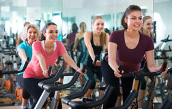 Females riding stationary bicycles. American females riding stationary bicycles in modern gym for women Stock Images