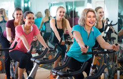 Females riding stationary bicycles Royalty Free Stock Photo